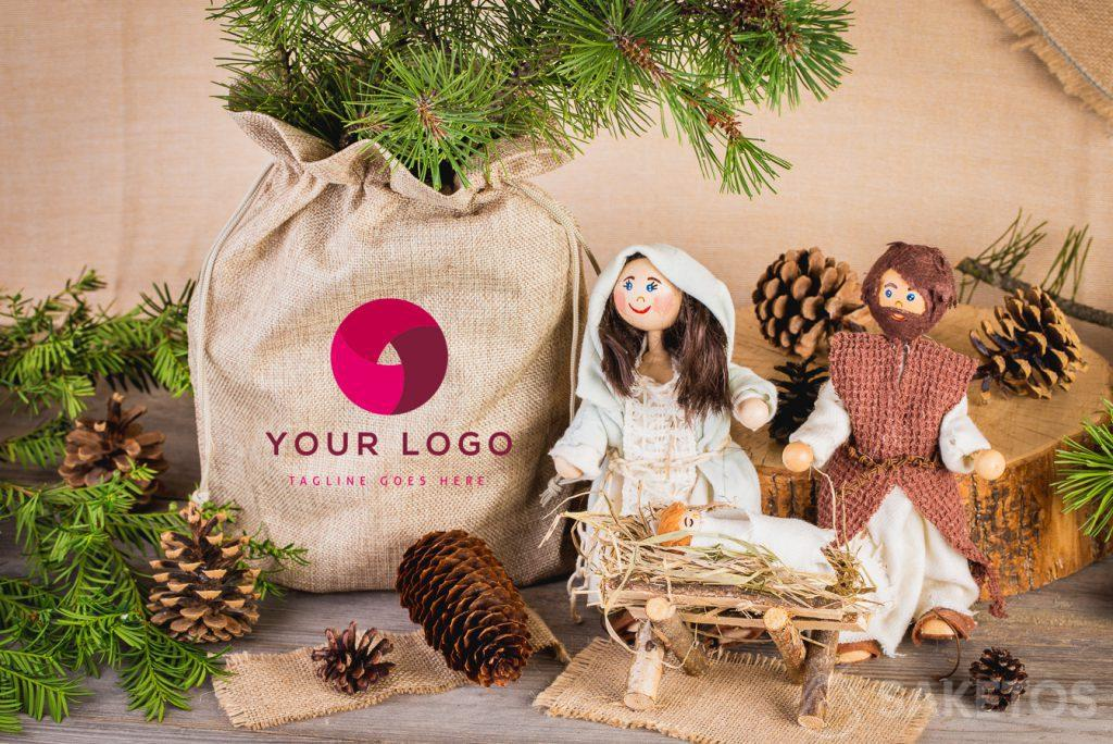 A Christmas nativity scene and a vase with a coniferous branch placed in a burlap bag