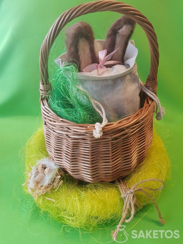 Basket with a linen pouch from which the ears of a felt worsted bun are protruding.