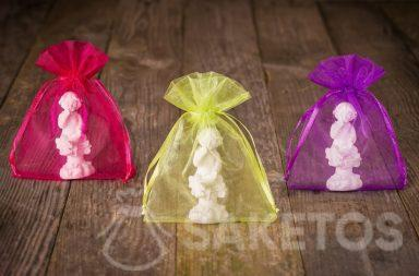 Figurines of angels packed in colorful organza pouch for thanks to wedding guests