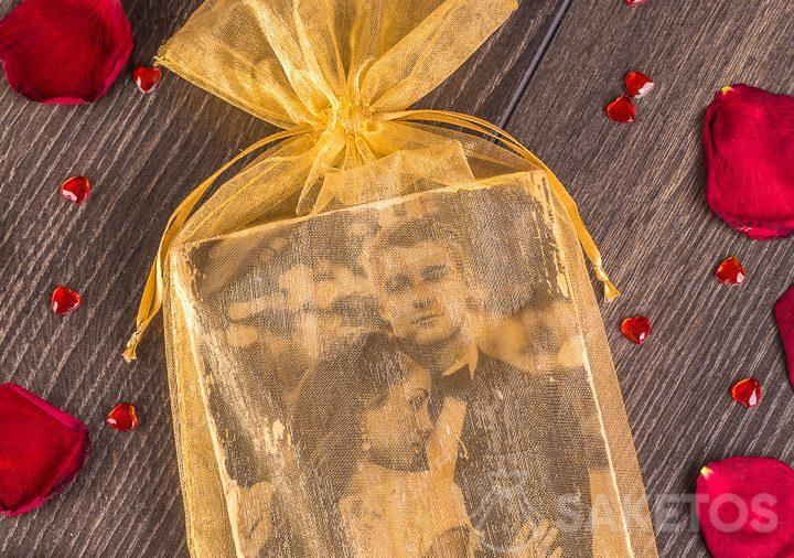 An elegant, golden organza pouch as a presentation bag for a honeymoon photo.