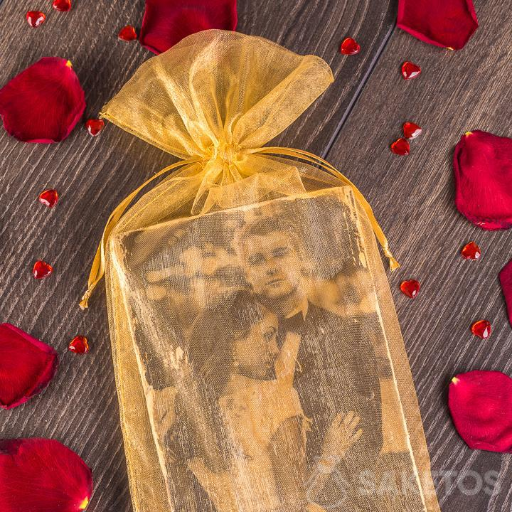 An elegant, golden organza pouch as a presentation bag for a honeymoon photo.