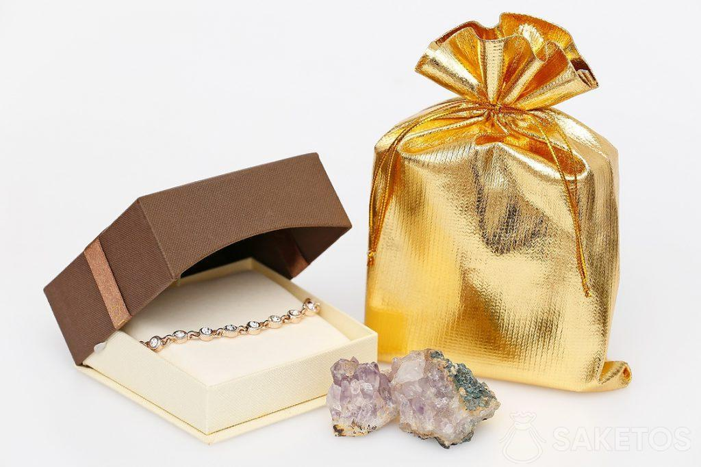 Silver satin bag as an elegant packaging for a cardboard jewelry box with earrings.