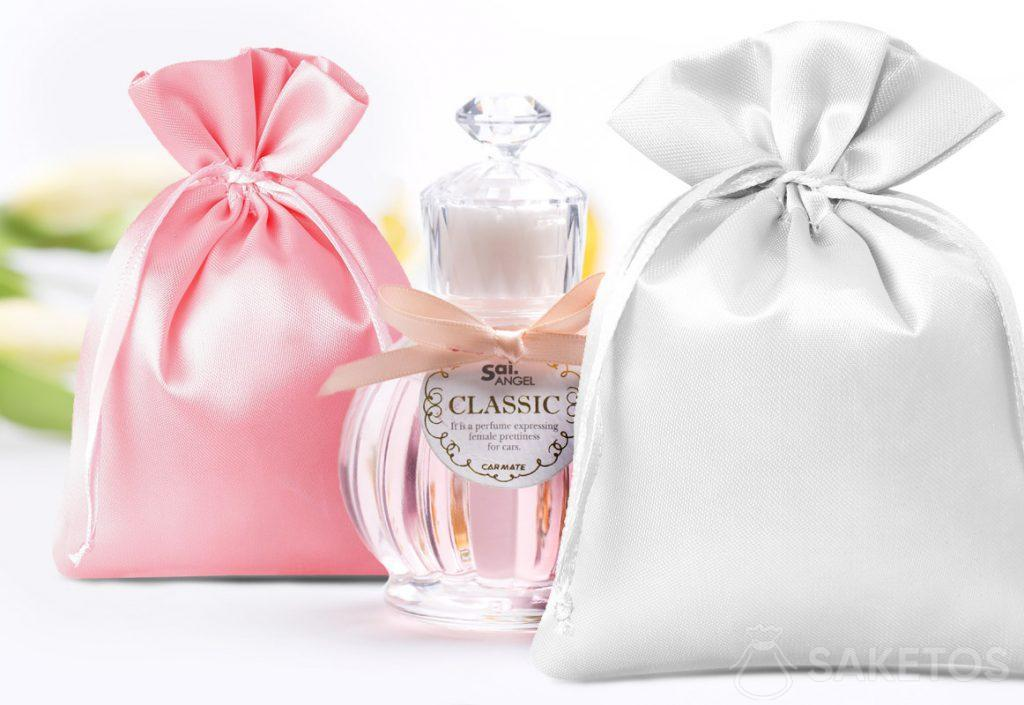Satin pouches in pink and silver and a decorative perfume bottle