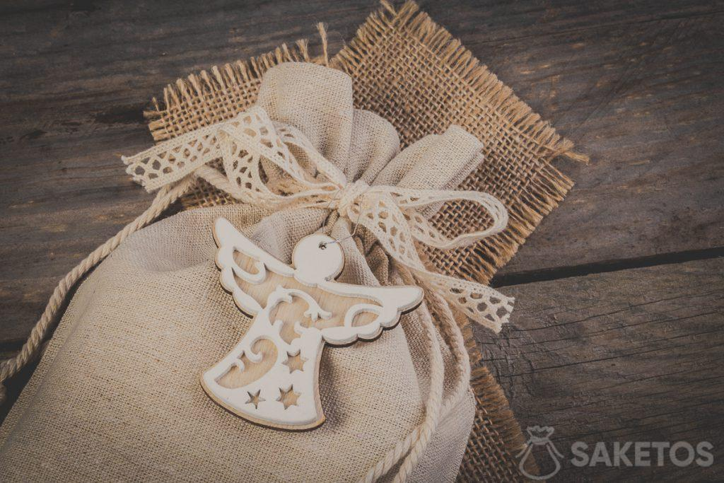 Linen bag tied with a decorative ribbon bow featuring a decorative pendant