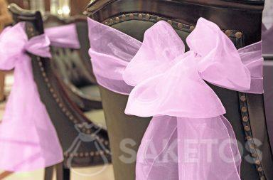 Decorative organza bow tied on the back of a chair