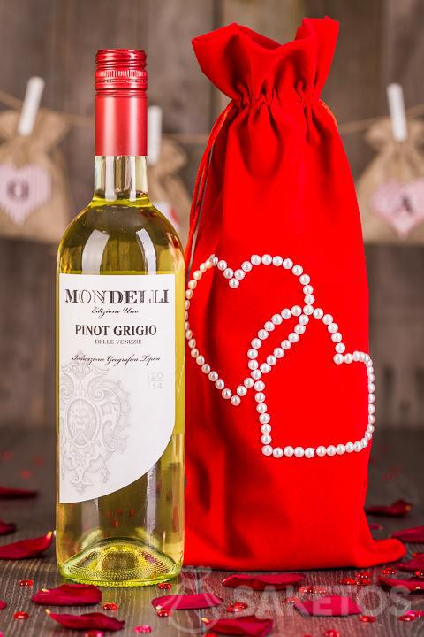 Wine wrapped as a gift in a decorative bag made of red velour