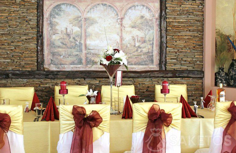 Decorative tableware in burgundy - a vase, napkins, candlesticks and bows on chairs