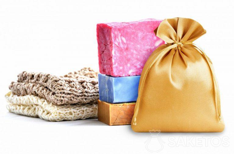 Golden satin bag in the background with colorful soaps.