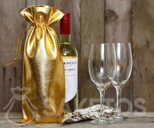 A bottle of wine wrapped in a gold metallic bag