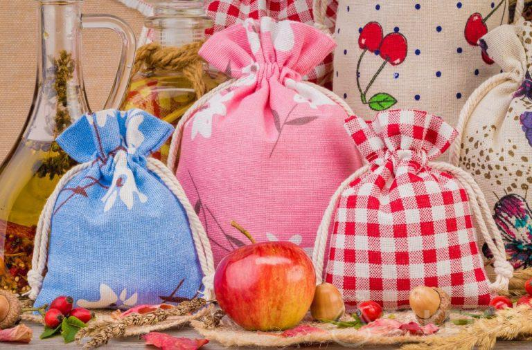 Linen bags with colourful prints for home decorations. An organza bag makes an elegant packaging option for a candle