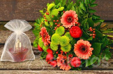 A gift set for a woman - a bouquet of flowers and perfume in an organza bag