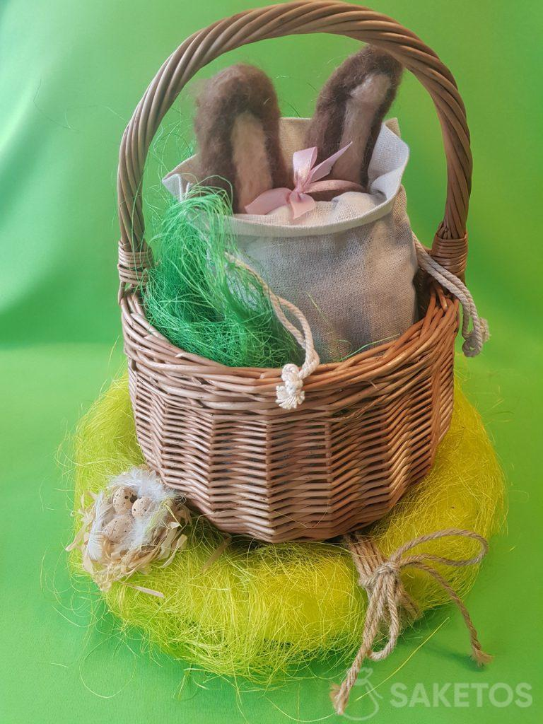 A basket with a linen bag, from which the ears of felt bunny wool stick out.