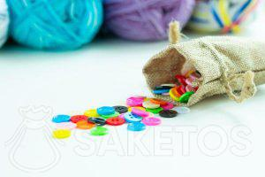 Coloured buttons in a jute bag